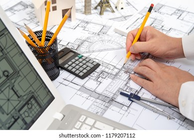 The hand of a male architect drawing a design using a pencil