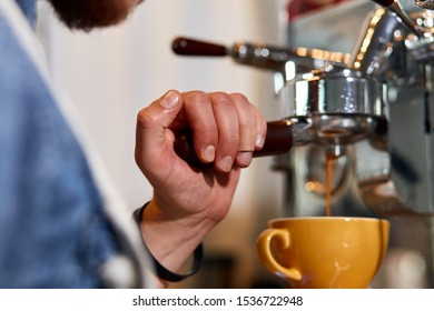 Hand of male barista with plaster on finger, keeps tamper on coffee machine, presses hot tasty americano into big beautiful cup, professional concept