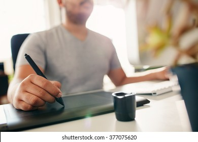 Hand of male designer working at his desk using stylus and digital graphics tablet.