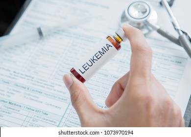 Hand of male doctor holding a small bottle of drug for Leukemia disease with medical record form background in the hospital