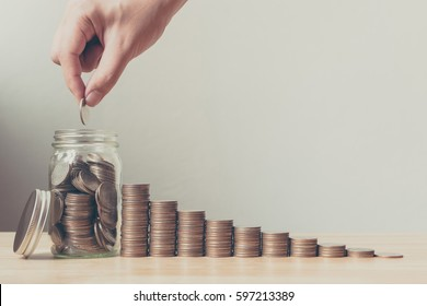 Hand of male or female putting coins in jar with money stack step growing growth saving money, Concept finance business investment