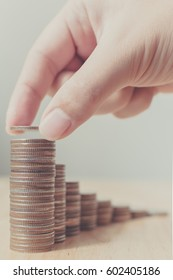Hand of male or female putting coins on money stack first step growing growth saving money, Concept finance business investment