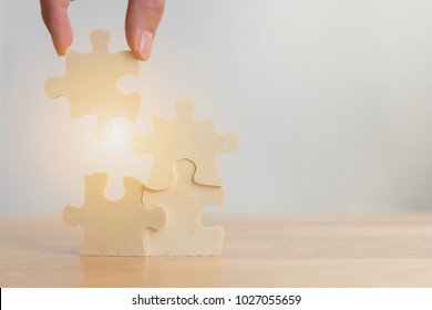 Hand of male or female putting jigsaw puzzle connecting on woodden desk, Strategic management and business solutions for success