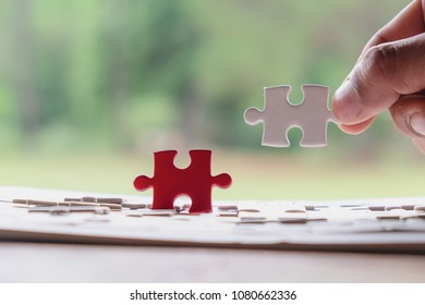 Hand of male or female putting jigsaw puzzle connecting on wooden desk and nature background, Strategic management and business solutions for success