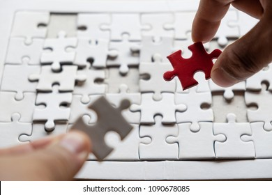 Hand of male or female putting jigsaw puzzle connecting on wooden desk, Strategic management and business solutions for success