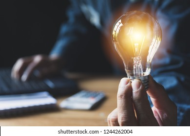 Hand of male holding a light bulb for accounting and creative concept.