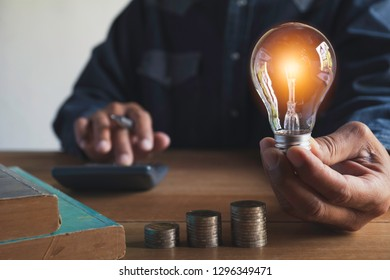 Hand of male holding a light bulb with stack of coins for accounting and creative concept.