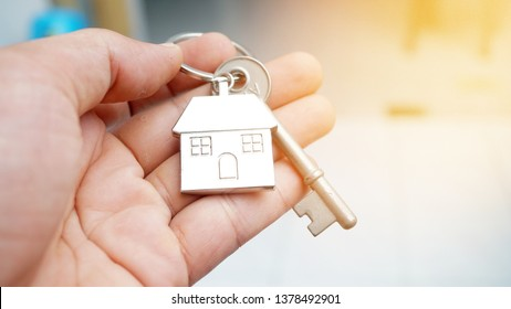 Hand of a male holding a new house key. Success concept