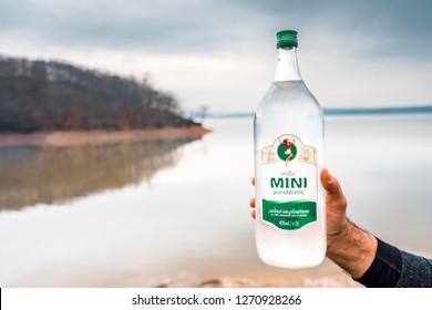 Hand of male holding two liter bottle of Greek anise alcoholic beverage ouzo on blurred istanbul omerli lake  background. Istanbul 2018.