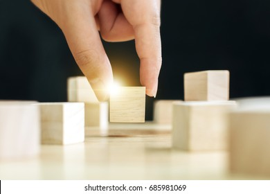 Hand of male pick up on one wooden block from many, Business ideas for choosing something that looks distinctive concept