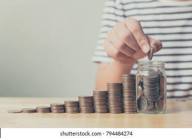 Hand of male putting coin in jar with money stack step growing growth saving money, Concept finance business investment