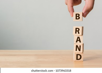 Hand of male putting wood cube block with word BRAND on wooden table. Brand building for success concept