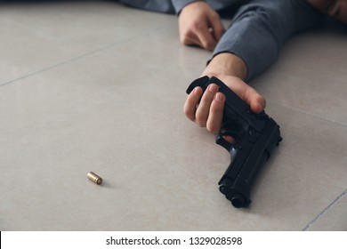Hand of male suicider with gun and bullet on floor