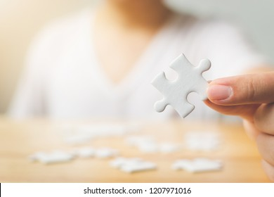 Hand of male trying to connect pieces of white puzzle on wooden table. Healthcare for alzheimer disease, dementia, memory loss, autism awareness and mental health concept