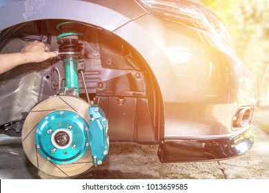 Hand and man adjust nut for level of  suspension repair concept and maintenance of car sunset light background