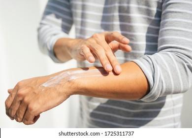 Hand eines Mannes, der Creme-Lotion auf den Armen aufträgt, um die Haut vor UV-Sonnenlicht zu schützen. Sonnenschutz. Flasche mit Lotion. Sonnenschutz auf der Hand.