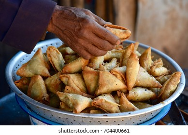 A hand of the man buying fried samosa pies at the rural food market at Inle Lake in Myanmar. Close up.