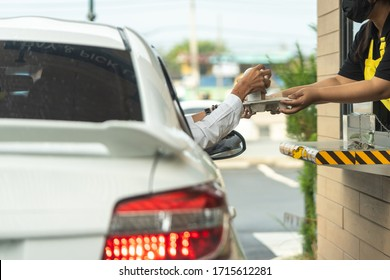 Hand of man from the car is picking a cup of coffee from the salesman by driving through or drive thru. (Social distancing)