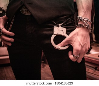 The hand of a man with a chain on his wrist and rings on his fingers holds handcuffs hanging from his trouser pockets. Attributes of rock musicians.
