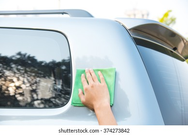 Hand with man cleaning car with green microfiber cloth