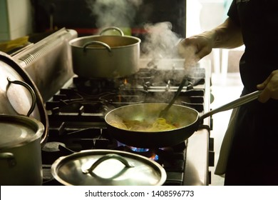 Hand man cooking with a steel pot on the stove in the kitchen
