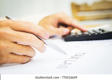 Hand man doing calculate and thinking on desk about tax at home office.