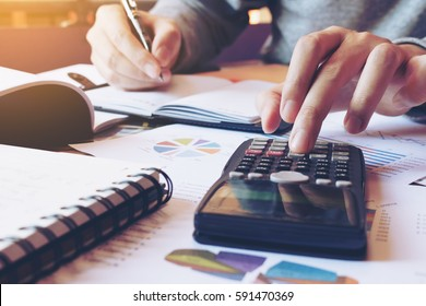 Hand man doing finances and calculate on desk about cost at home office. - Shutterstock ID 591470369