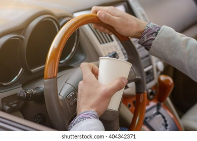 hand man driving an expensive car with a cup of coffee