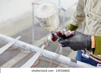 Hand of man in glove with spray paint gun, painting car details