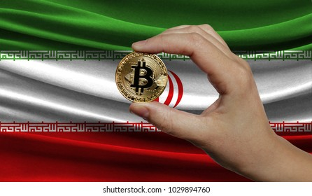 Hand of a man with a gold bitcone Cryptocurrency Digital bit of coins in a hand on a background of the flag of Iran.