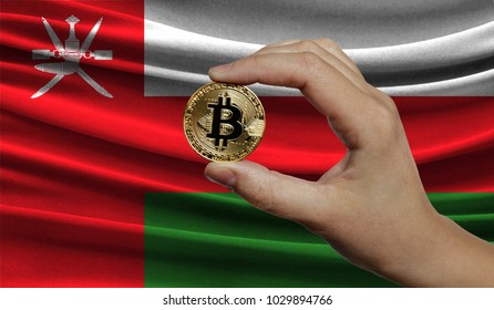 Hand of a man with a gold bitcone Cryptocurrency Digital bit of coins in a hand on a background of the flag of Oman.