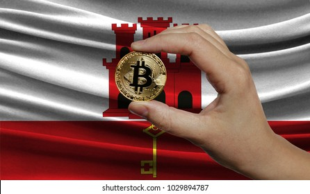 Hand of a man with a gold bitcone Cryptocurrency Digital bit of coins in a hand on a background of the flag of Gibraltar.