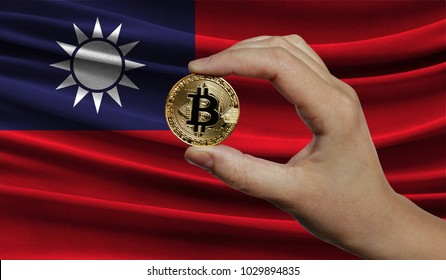 Hand of a man with a gold bitcone Cryptocurrency Digital bit of coins in a hand on a background of the flag of Taiwan.