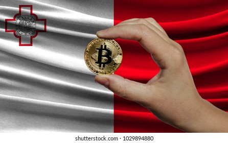 Hand of a man with a gold bitcone Cryptocurrency Digital bit of coins in a hand on a background of the flag of malta.