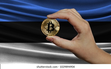 Hand of a man with a gold bitcone Cryptocurrency Digital bit of coins in a hand on a background of the flag of Estonia.