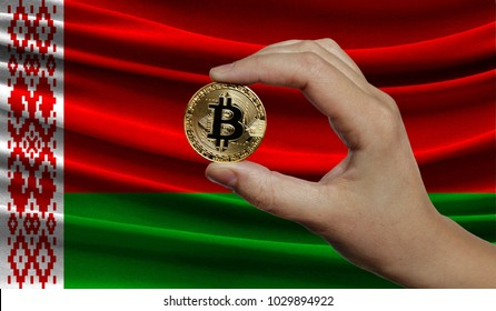 Hand of a man with a gold bitcone Cryptocurrency Digital bit of coins in a hand on a background of the flag of Belarus.