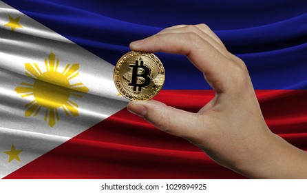 Hand of a man with a gold bitcone Cryptocurrency Digital bit of coins in a hand on a background of the flag of Philippines.