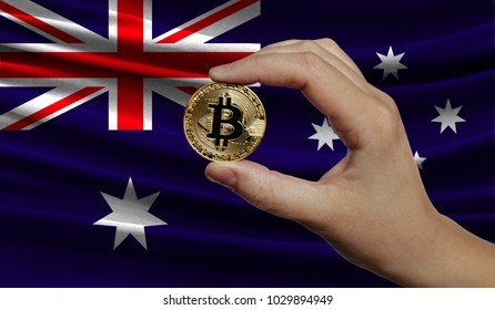 Hand of a man with a gold bitcone Cryptocurrency Digital bit of coins in a hand on a background of the flag of Australia.