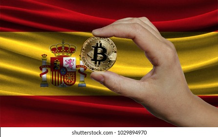 Hand of a man with a gold bitcone Cryptocurrency Digital bit of coins in a hand on a background of the flag of Spain.