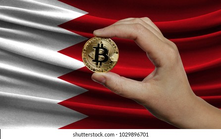 Hand of a man with a gold bitcone Cryptocurrency Digital bit of coins in a hand on a background of the flag of Bahrain.