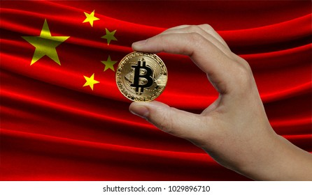 Hand of a man with a gold bitcone Cryptocurrency Digital bit of coins in a hand on a background of the flag of China.