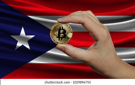 Hand of a man with a gold bitcone Cryptocurrency Digital bit of coins in a hand on a background of the flag of Puerto Rico.