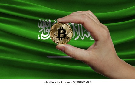 Hand of a man with a gold bitcone Cryptocurrency Digital bit of coins in a hand on a background of the flag of Saudi Arabia.