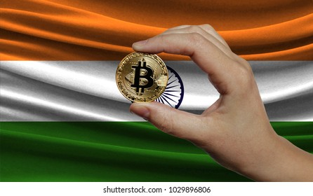 Hand of a man with a gold bitcone Cryptocurrency Digital bit of coins in a hand on a background of the flag of India.