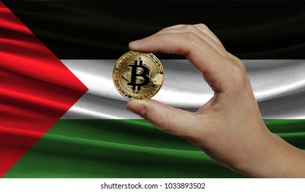 Hand of a man with a gold bitcone Cryptocurrency Digital bit of coins in a hand on a background of the flag of Palestine.