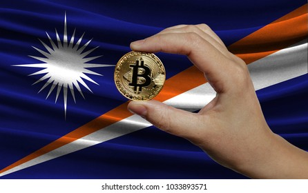 Hand of a man with a gold bitcone Cryptocurrency Digital bit of coins in a hand on a background of the flag of Marshall Islands.