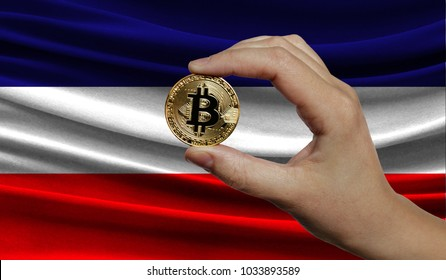 Hand of a man with a gold bitcone Cryptocurrency Digital bit of coins in a hand on a background of the flag of Los Altos.