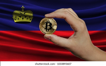 Hand of a man with a gold bitcone Cryptocurrency Digital bit of coins in a hand on a background of the flag of Liechtenstein.