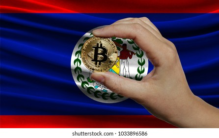 Hand of a man with a gold bitcone Cryptocurrency Digital bit of coins in a hand on a background of the flag of Belize.