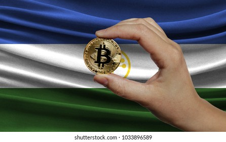 Hand of a man with a gold bitcone Cryptocurrency Digital bit of coins in a hand on a background of the flag of Bashkortostan.